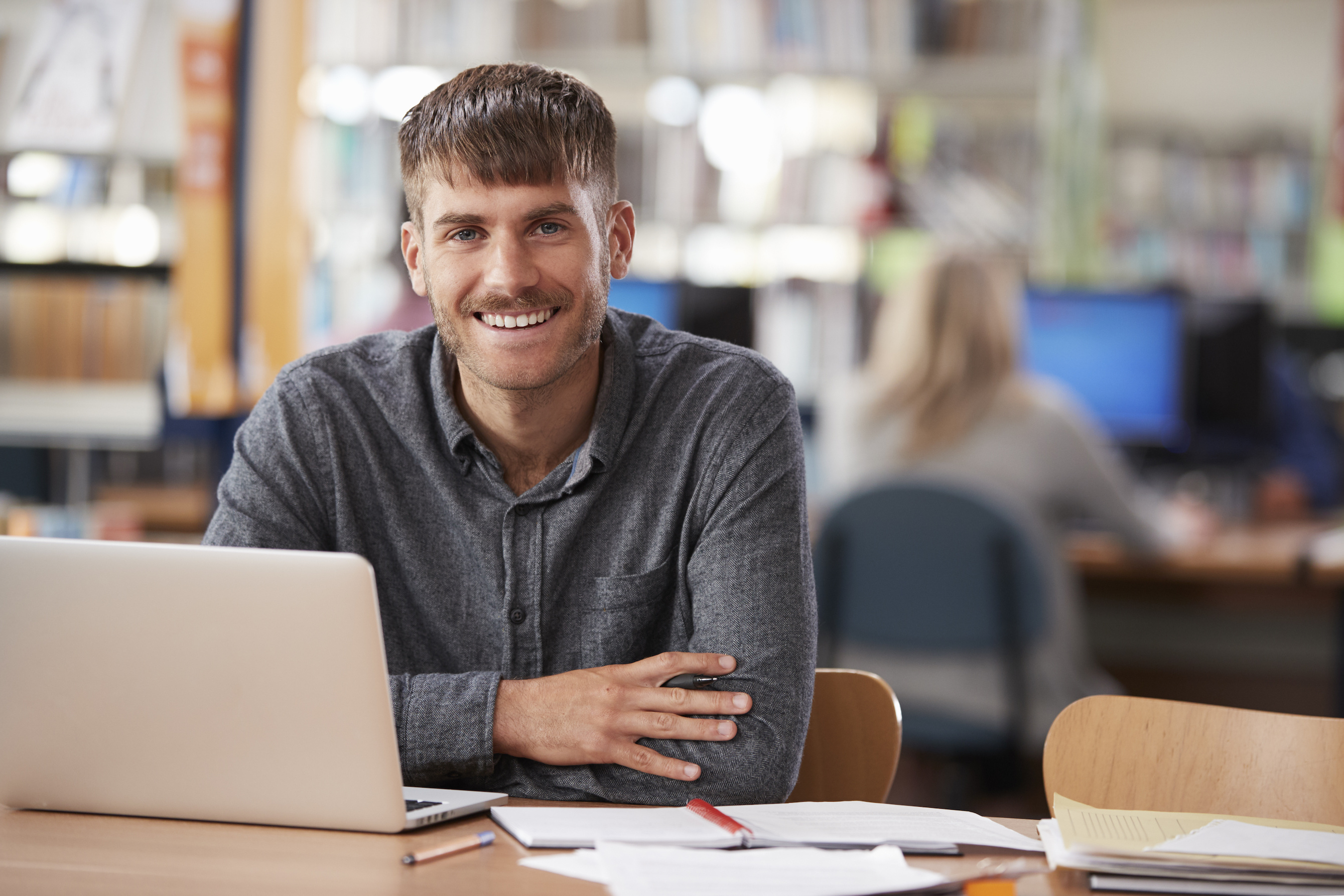 Smiling male teacher at desk
